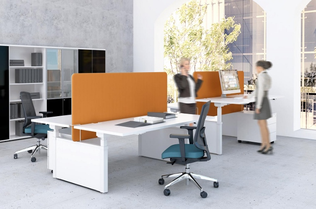 Image of four height adjustable desks, linked in blocks of two.